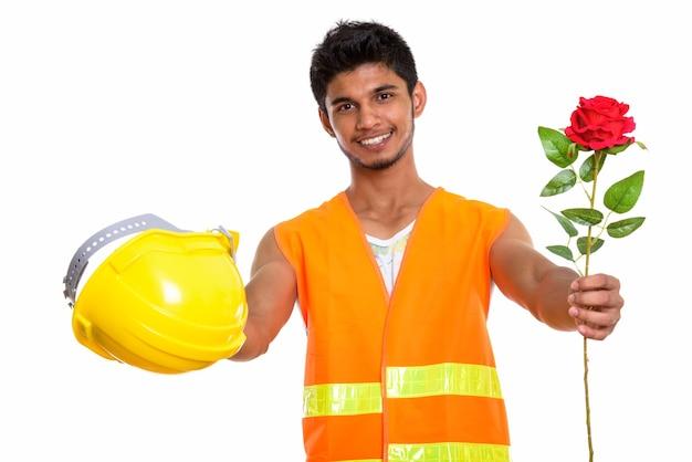Joven trabajador de la construcción indio feliz sonriendo mientras da rosa roja