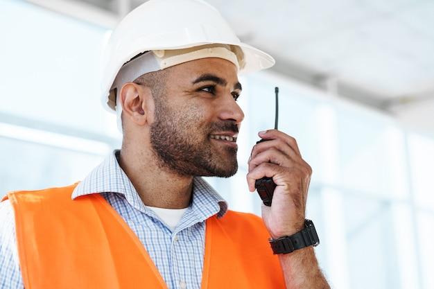 Joven trabajador de la construcción en uniforme con walkie talkie en el sitio