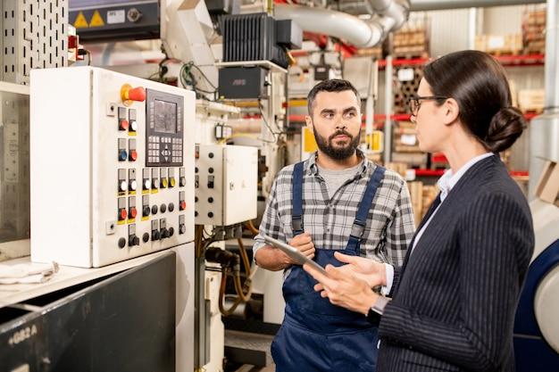 Joven trabajador de una fábrica contemporánea consultando a su socio sobre nuevos métodos de procesamiento de materia prima