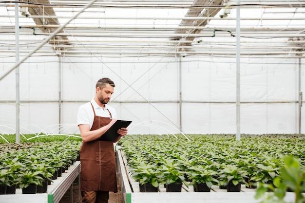 Joven trabajador haciendo investigación con plantas
