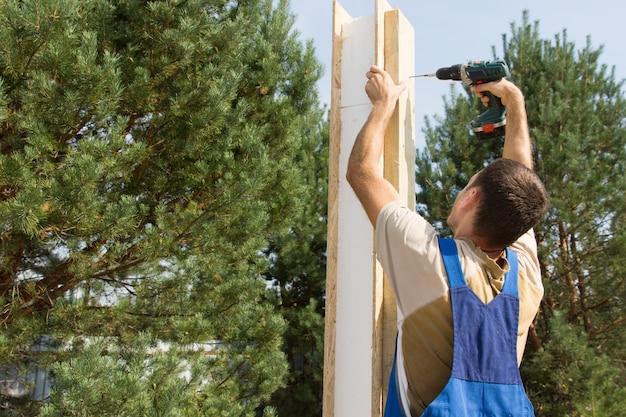 Joven trabajador manual de perforación de un poste de madera en el sitio de construcción.