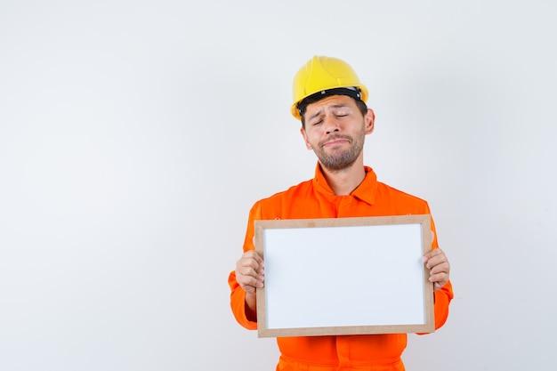 Joven trabajador con marco en blanco en uniforme, casco y con cara de tristeza.