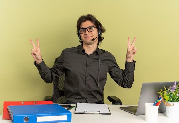Joven trabajador de oficina complacido en auriculares con gafas ópticas se sienta en el escritorio con herramientas de oficina usando laptop y gestos signo de mano de victoria aislado sobre fondo verde con espacio de copia