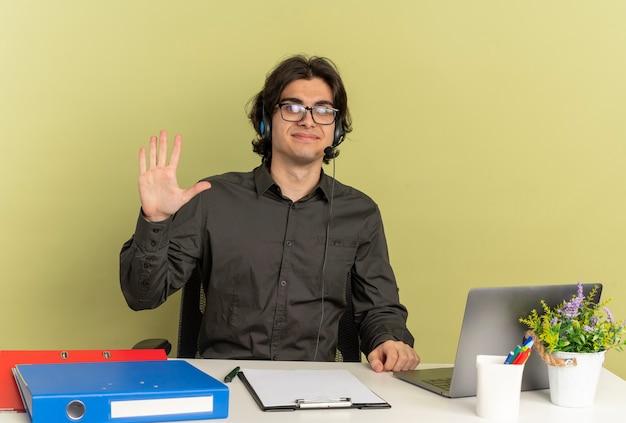 Joven trabajador de oficina complacido en auriculares con gafas ópticas se sienta en el escritorio con herramientas de oficina usando laptop levanta la mano mirando a cámara aislada sobre fondo verde con espacio de copia