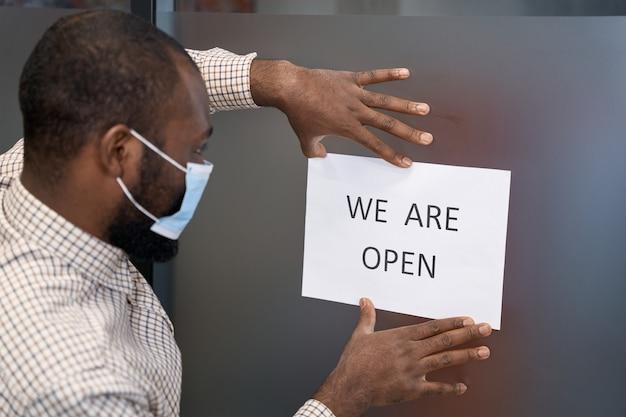 Joven trabajador de oficina masculino afroamericano vistiendo mascarilla protectora pegada cartel abierto con