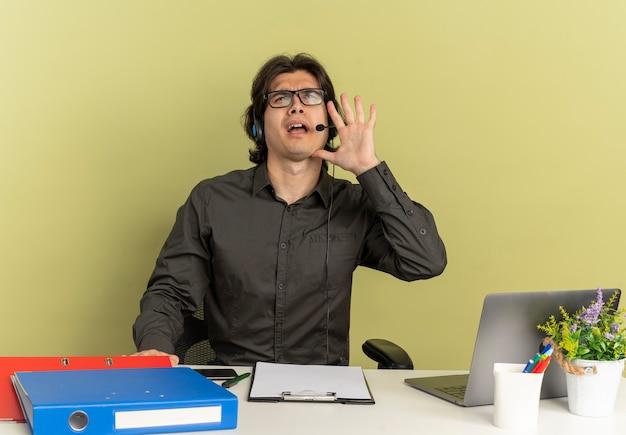 Joven trabajador de oficina molesto en auriculares se sienta en el escritorio con herramientas de oficina usando laptop pretendiendo llamar a alguien aislado sobre fondo verde con espacio de copia