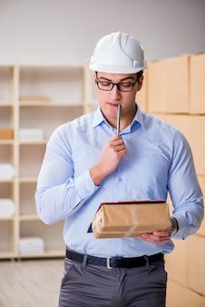 Joven trabajador en la oficina postal que se ocupa de paquetes