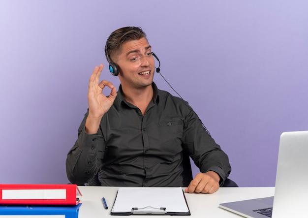 Joven trabajador de oficina rubio complacido en auriculares se sienta en el escritorio con herramientas de oficina mirando gestos de portátil signo de mano ok aislado sobre fondo violeta con espacio de copia