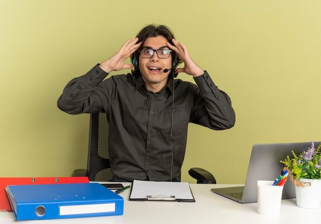 Joven trabajador de oficina sorprendido en auriculares con gafas se sienta en el escritorio con herramientas de oficina usando laptop sostiene la cabeza mirando a cámara aislada sobre fondo verde con espacio de copia