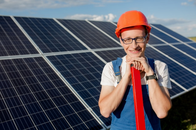Joven trabajador de pie en la estación de energía solar en el campo.