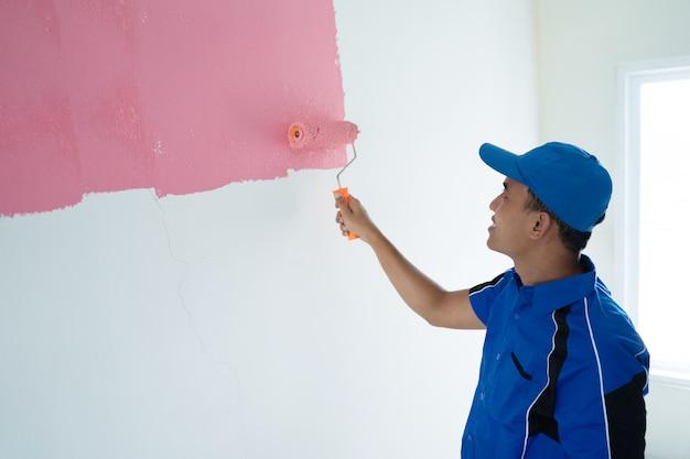Joven trabajador pintando en la pared