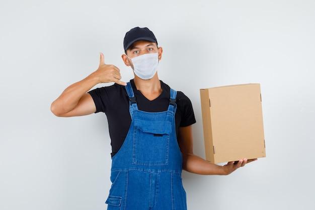 Joven trabajador sosteniendo una caja de cartón con gesto de teléfono en uniforme, vista frontal de la máscara.