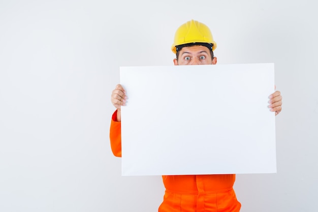 Joven trabajador sosteniendo un lienzo en blanco en uniforme, casco y mirando desconcertado.