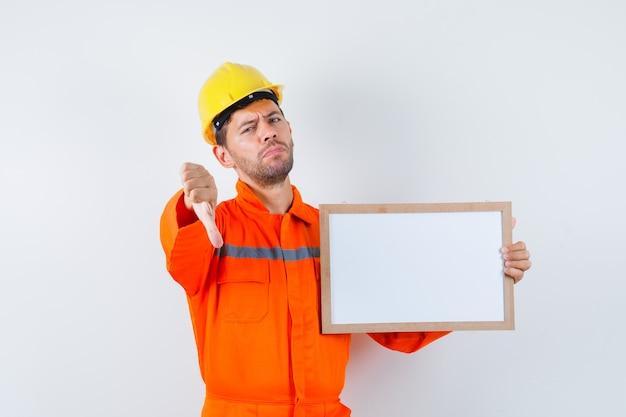 Joven trabajador sosteniendo el marco en blanco, mostrando el pulgar hacia abajo en uniforme, casco.