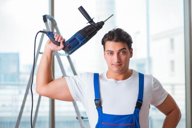 Joven trabajador con taladro de mano