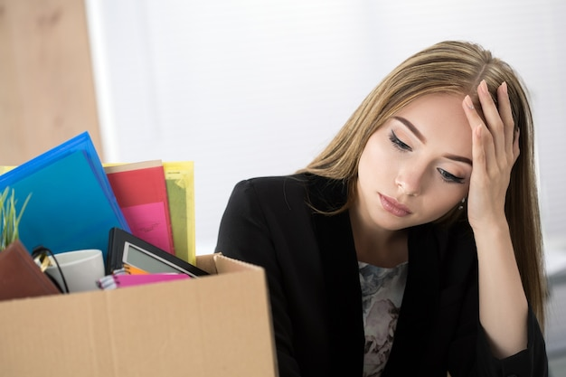 Joven trabajadora despedida en la oficina sentada cerca de una caja de cartón con sus pertenencias. conseguir el concepto despedido.