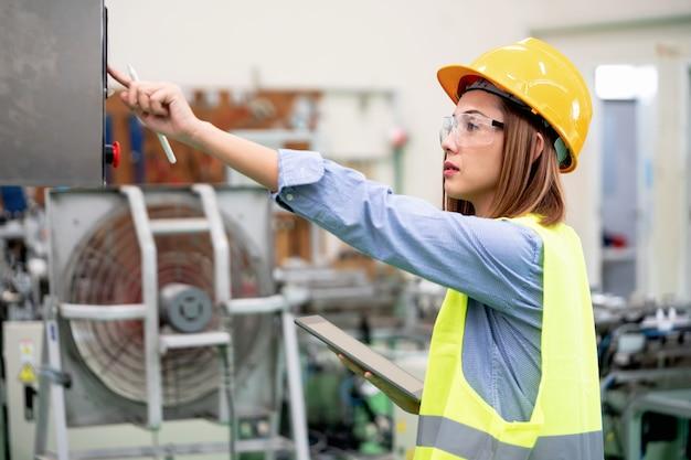 Joven trabajadora feliz en tableta de uso de fábrica programa de comprobación antes del envío. inspección de control de calidad