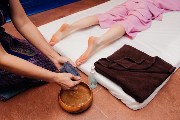 La joven trabajadora masajista tailandesa en traje exótico étnico asiático hace y demuestra diferentes elementos de procedimientos de spa tradicionales a la bella dama blanca en pijama rosa en la sala de yoga azul