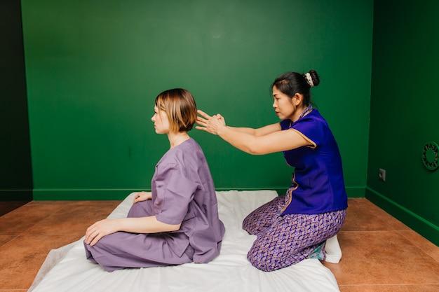 La joven trabajadora masajista tailandesa en traje exótico étnico asiático hace y demuestra diferentes procedimientos de spa tradicionales en la sala de yoga de relajación verde