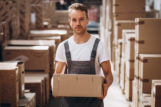 Joven trabajando en un almacén con cajas