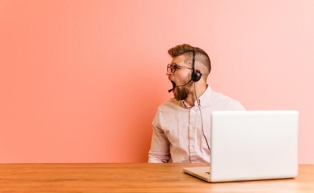 Joven trabajando en un call center gritando hacia un espacio en blanco