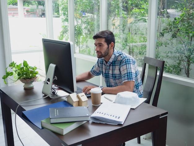 Joven trabajando en casa con café y periódico