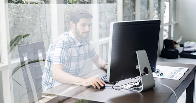 Joven trabajando desde casa por computadora.
