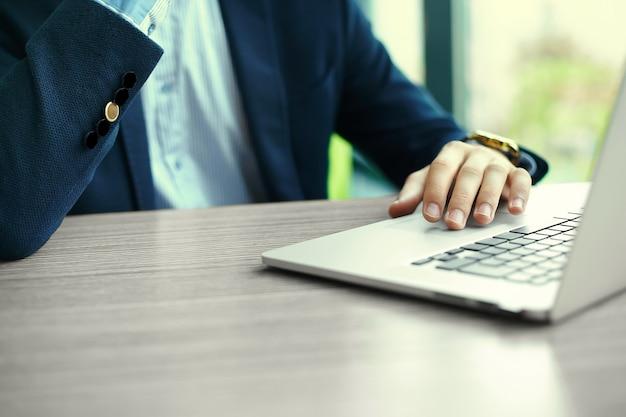 Joven trabajando con la computadora portátil, las manos del hombre en la computadora portátil, persona de negocios en el lugar de trabajo
