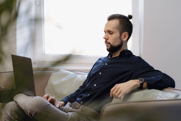 Joven trabajando en la computadora portátil mientras está sentado en el sofá de la oficina