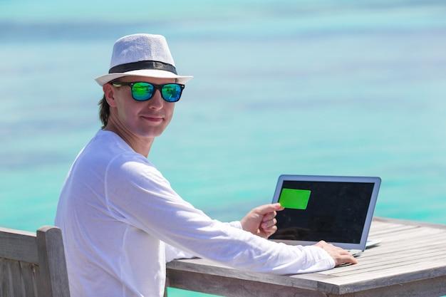 Joven trabajando en la computadora portátil con tarjeta de crédito en playa tropical
