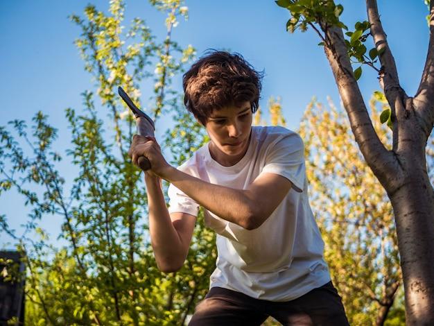 Joven trabajando en el jardín con hacha cerca del árbol