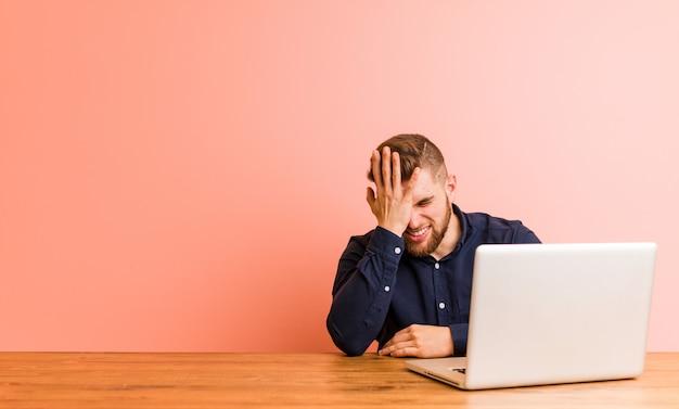 Joven trabajando con su computadora portátil olvidando algo, golpeándose la frente con la palma y cerrando los ojos.