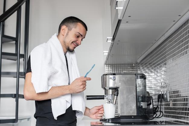 El joven va a trabajar por la mañana. se cepilla los dientes cerca de una cafetera mientras espera una taza de café