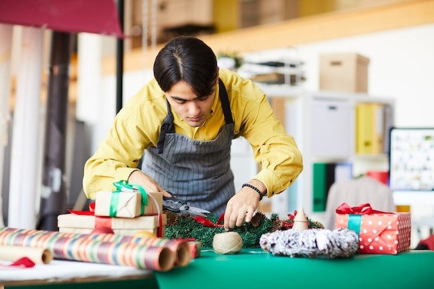 Joven en el trabajo, haciendo una corona de navidad y envolviendo regalos