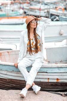 Una joven con un traje blanco se sienta en la popa de un barco de recreo.