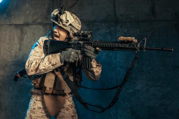 Joven en traje militar un soldado mercenario en los tiempos modernos en una pared oscura en studio