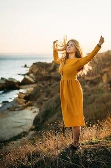 Una joven tranquila se encuentra al borde de un acantilado con un vestido largo amarillo con las manos en alto