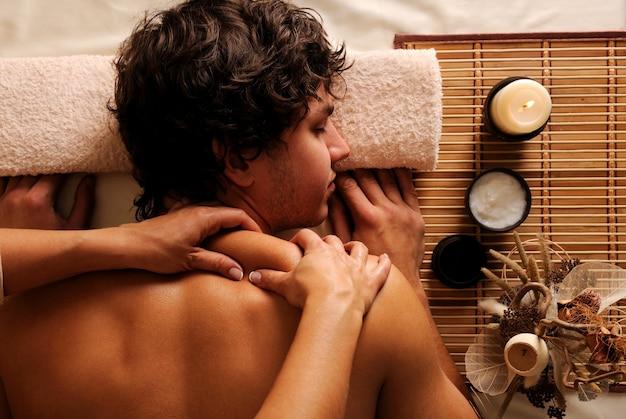 El joven en tratamiento de spa: recreación, descanso, relajación y masaje. vista de ángulo de hygh