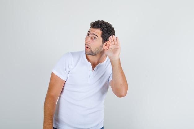 Joven tratando de escuchar algo confidencial en camiseta blanca y mirando astuto