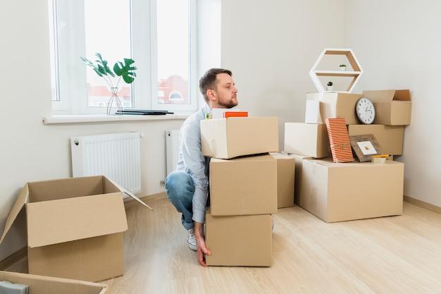 Joven tratando de llevar la pila de cajas de cartón en casa