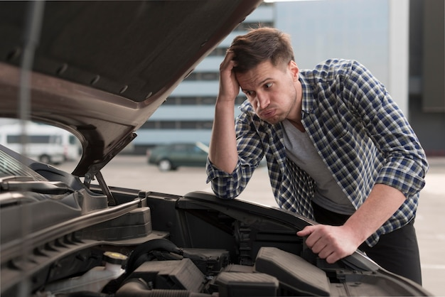 Joven tratando de reparar el auto