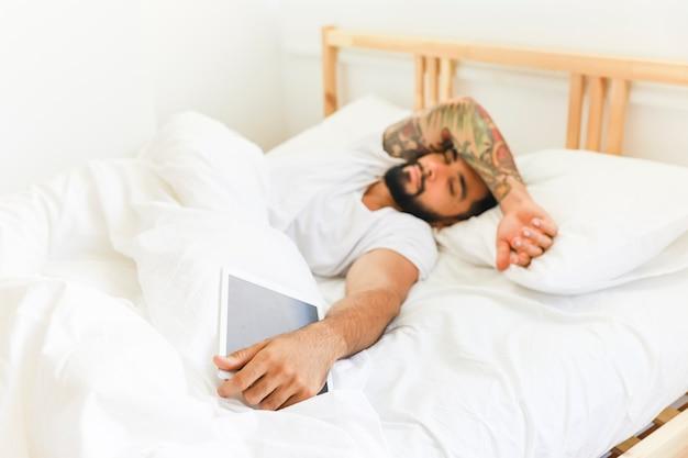 Joven tumbado en la cama con tableta digital