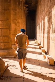 Joven con turbante azul caminando sobre las columnas del templo de edfu, cerca de la ciudad de asuán. egipto
