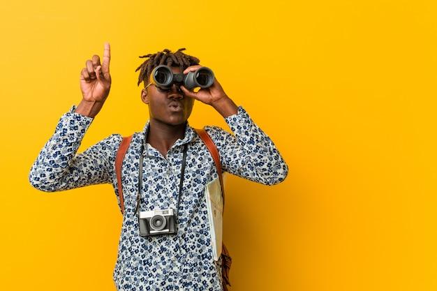 Joven turista africano hombre de pie en amarillo sosteniendo un binoculares