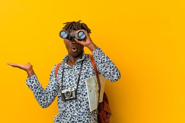 Joven turista africano hombre de pie contra un fondo amarillo sosteniendo un binoculares