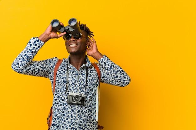 Joven turista africano hombre de pie contra una pared amarilla sosteniendo un binoculares