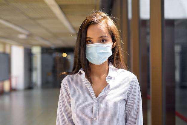 Joven turista asiática con máscara para protegerse del brote del virus corona en el aeropuerto