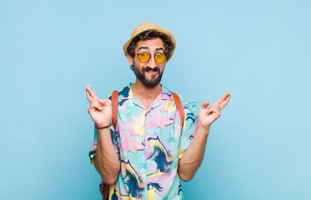 Joven turista barbudo cruzando los dedos con ansiedad y esperando buena suerte con una mirada preocupada