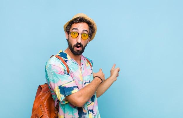 Joven turista barbudo que se siente conmocionado y sorprendido, apuntando al espacio de la copia en el costado con una mirada asombrada y con la boca abierta