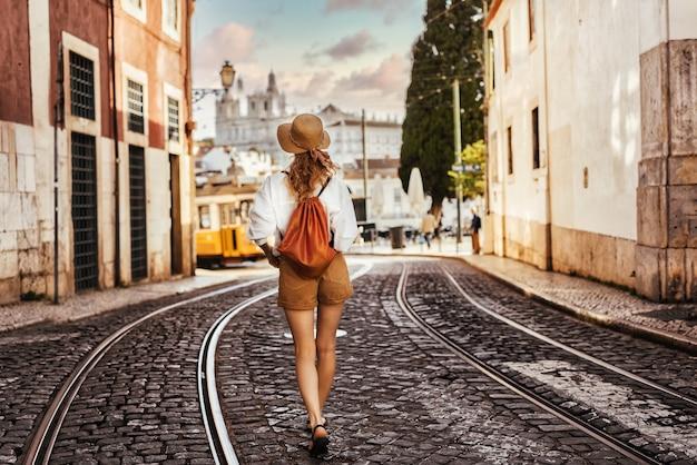 Joven turista caminando sobre las antiguas vías del tranvía en lisboa, portugal.